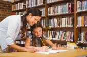 Teacher assisting girl with homework in library — Stock Photo