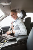 Businesswoman putting on her seat belt — Stock Photo