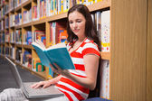 Student sitting on floor in library reading — Foto de Stock