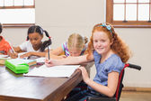 Cute pupils writing at desk in classroom  — Stock Photo