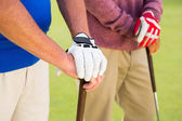 Golfing friends standing and holding clubs — Stock Photo
