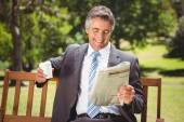 Businessman reading newspaper in the park — Stok fotoğraf