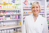 Smiling blonde pharmacist posing in lab coat — Stock Photo