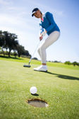 Female golfer putting her ball — Stock Photo