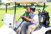 Golfing friends driving in their golf buggy — ストック写真