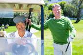 Happy golfing friends setting out smiling at camera on buggy — Stock Photo