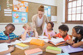Pretty teacher helping pupils in classroom — Stock Photo