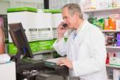 Senior pharmacist phoning while using computer — Stock Photo
