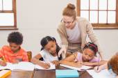 Cute pupils getting help from teacher in classroom  — Stock Photo