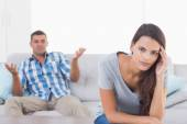 Woman suffering from headache while man quarreling — Stock Photo