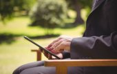 Businessman using tablet in the park — Stock Photo