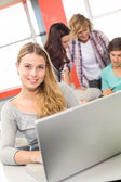 Female student using laptop in classroom — Stock Photo
