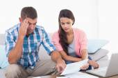 Couple reading bill while calculating home finances — Stock Photo