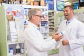 Smiling pharmacists holding medication — Stock Photo