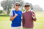 Golfing friends smiling at camera holding clubs — Stock Photo