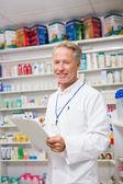 Senior pharmacist writing on clipboard — Stock Photo