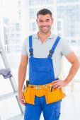 Handyman in overalls at modern office — Stockfoto