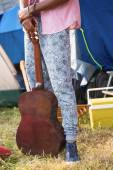 Hipster holding guitar at campsite — Stock Photo