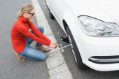Young woman replacing tire — Stock Photo