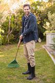 Handsome man raking in his garden — Stock Photo