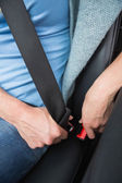 Woman putting on her seat belt  — Stock Photo