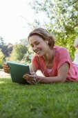 Pretty woman using tablet in park — Stock Photo