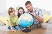 Family exploring globe — Stock Photo