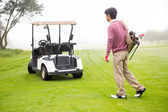 Golfing walking toward the buggy — 图库照片