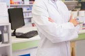 Mid section of junior pharmacist with arms crossed — Stock Photo