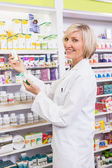 Smiling pharmacist holding boxes of medicine — Stock Photo