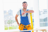Carpenter in overalls with spirit level — Stockfoto