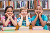 Cute pupils looking at camera in library — Stock Photo