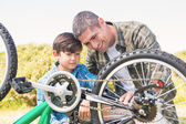 Father and son repairing bike — Stock Photo