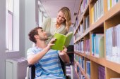 Smiling disabled student with classmate in library — Stock Photo