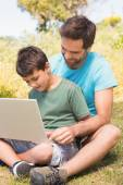 Father and son in the countryside using laptop — Stock Photo