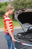 Worried young woman beside her broken down car — Stock Photo
