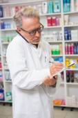 Focused pharmacist on the phone taking notes — Stock Photo