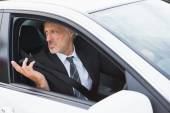 Perplexed businessman in the drivers seat — Stock Photo