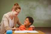 Teacher assisting little boy with homework in classroom — Stock Photo