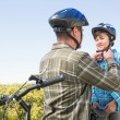 Father attaching his son cycling helmet — Stock Photo #68981927