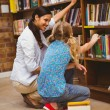 Teacher and little girl selecting book in library — Stock Photo #68982135
