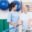 Senior woman walking with parallel bars with therapist  — Stock Photo #68982255