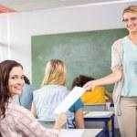 Teacher handing paper to student in class — Stock Photo #68982285