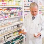 Smiling pharmacist looking at medications — Stock Photo #68982329
