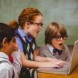 Shocked little school kids using laptop — Stock Photo #68983383