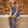Cute little girl reading book in library — Stock Photo #68984053