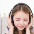 Girl with eyes closed listening music through headphones — Stock Photo #68984165