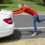 Young woman pushing her broken down car — Stock Photo #68985943