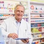 Smiling pharmacist using tablet pc — Stock Photo #68986091