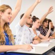 Students raising hands in classroom — Stock Photo #68986697
